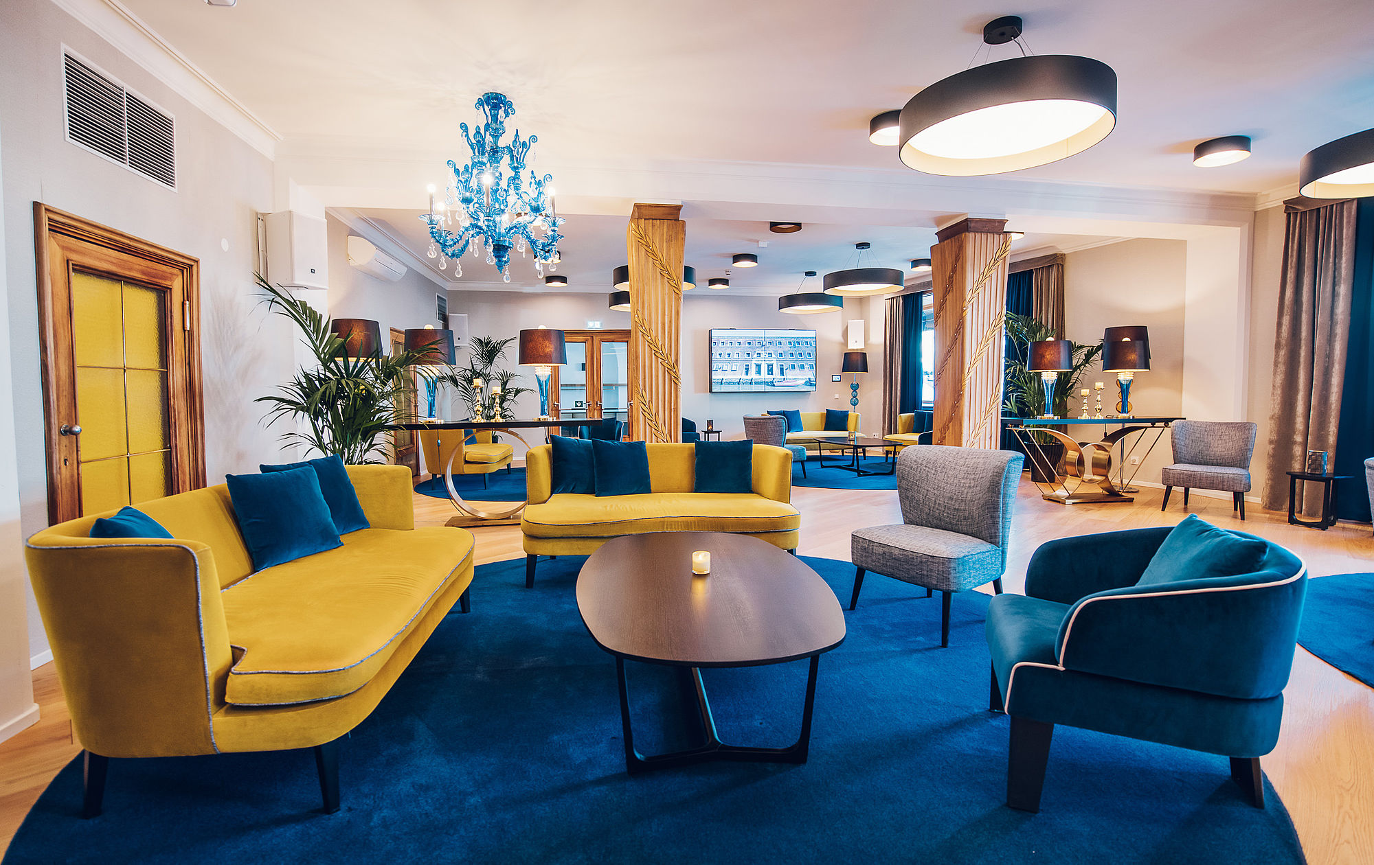 Interior view of the Hotel Stein Lounge with stylish furniture, blue floor lamps and artfully decorated column.