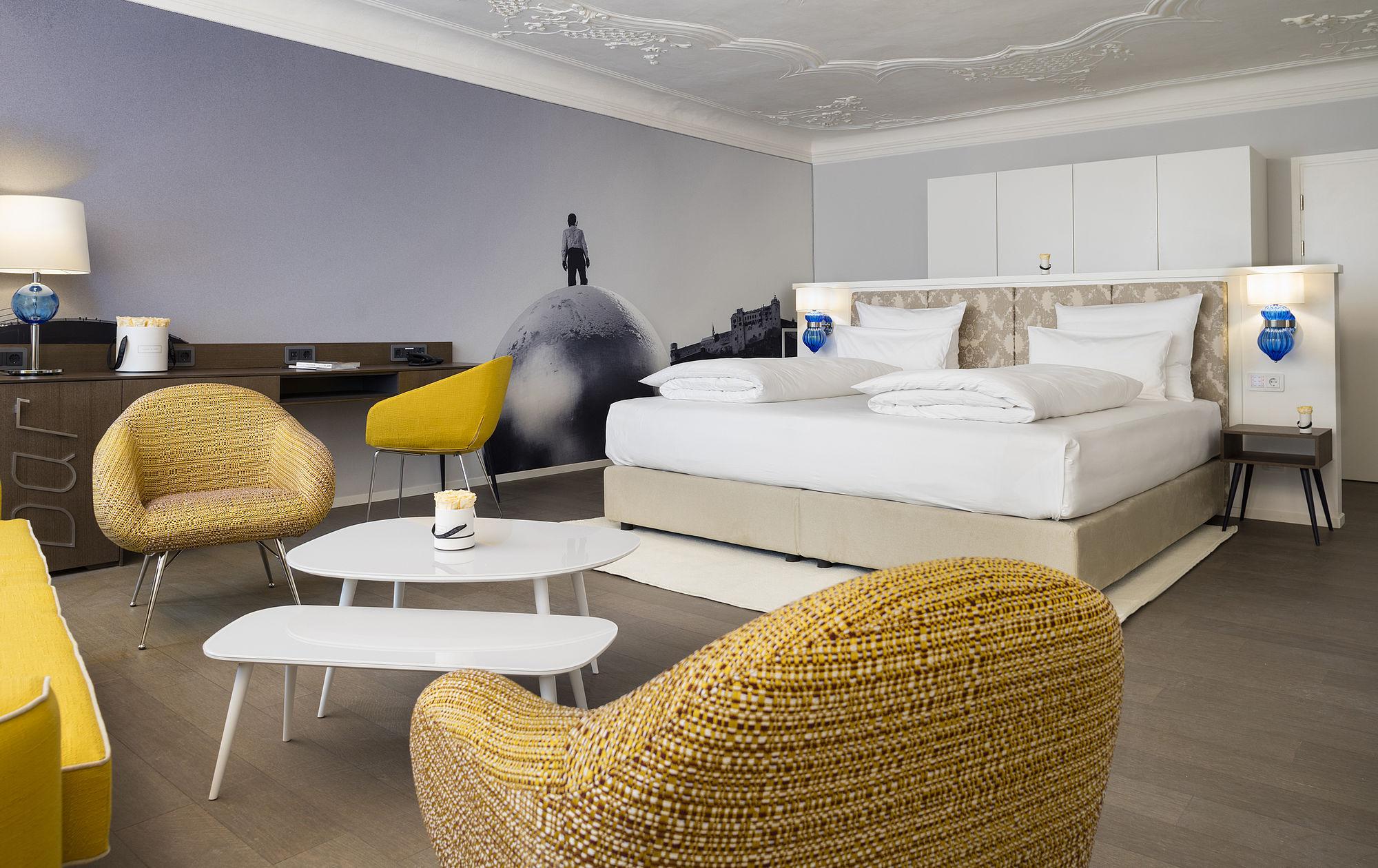 Geräumige Hotel Suite Mit Blick Aufs Doppelbett Und Stuckverzierter Decke  In Salzburg.
